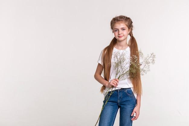 Garotinha tranquila. menina bonita e magra com cabelo comprido claro, vestindo jeans e segurando um ramo de flores do campo