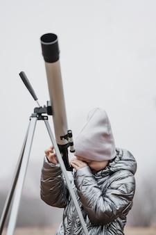 Garotinha usando um telescópio de frente