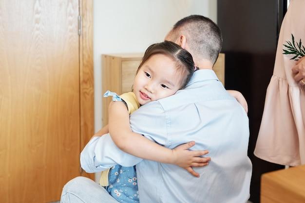 Garotinha vietnamita adorável e feliz abraçando o pai, que acabou de chegar do trabalho