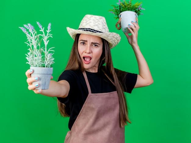 Garotinha zangada e linda jardineira de uniforme, usando chapéu de jardinagem, levantando e segurando flores para a câmera em um vaso isolado no fundo verde