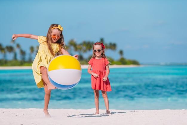 Garotinhas adoráveis brincando na praia com bola de ar