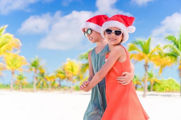 Garotinhas adoráveis em chapéus de papai noel durante as férias de praia se divertir juntos