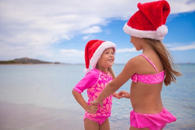 Garotinhas adoráveis em chapéus de papai noel durante as férias de praia