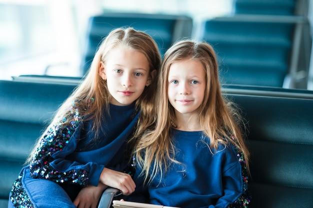 Garotinhas adoráveis no aeroporto à espera de embarque perto de grande janela