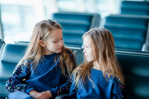 Garotinhas adoráveis no aeroporto perto de grande janela