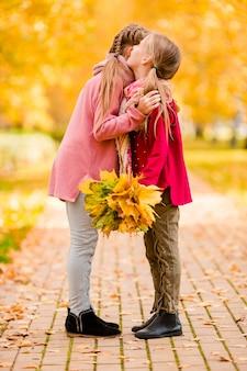 Garotinhas adoráveis no dia quente no outono parque ao ar livre