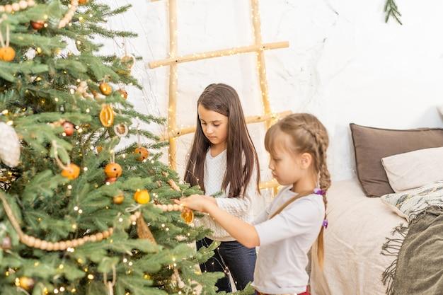 Garotinhas adoráveis perto de uma árvore de natal em uma aconchegante sala de estar no inverno