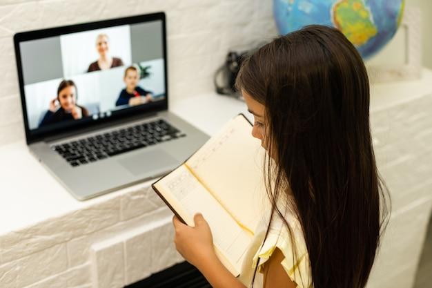 Garotinhas alegres usando um laptop, estudando por meio de um sistema de e-learning on-line