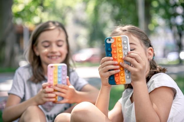 Garotinhas ao ar livre com telefones em uma caixa com espinhas estouram, um brinquedo antiestresse da moda.