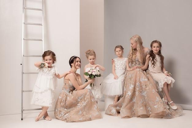 Garotinhas bonitas com flores vestidas de noiva