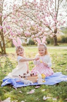 Garotinhas bonitas estão sentadas na grama perto da mogólia. meninas em fantasias coelhinhos da páscoa. primavera.