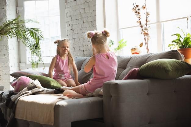Garotinhas calmas acordando em um quarto de pijama fofo, estilo caseiro e conforto