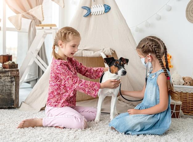 Garotinhas com estetoscópio ouvindo cachorro como um médico sentado no chão na sala de jogos