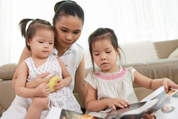 Garotinhas curiosas e a mãe olhando livro de fotos impressas
