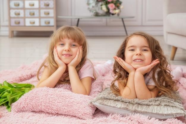 Garotinhas de aparência caucasiana brincam sentadas no chão em uma sala bem iluminada em estilo escandinavo com um buquê de flores