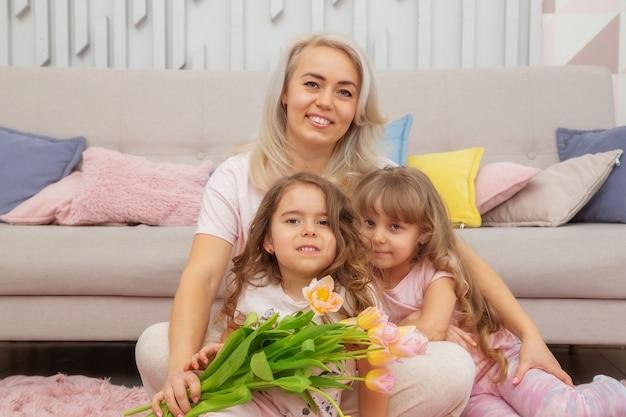 Garotinhas de aparência caucasiana se abraçam à mãe, sentadas no chão em frente ao sofá em uma sala bem iluminada em estilo escandinavo