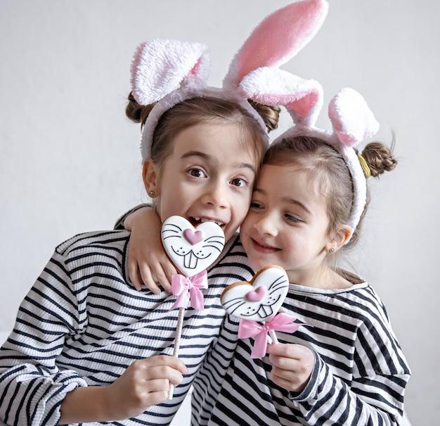 Garotinhas engraçadas com orelhas de páscoa nas cabeças e pão de mel de páscoa em palitos. Foto gratuita