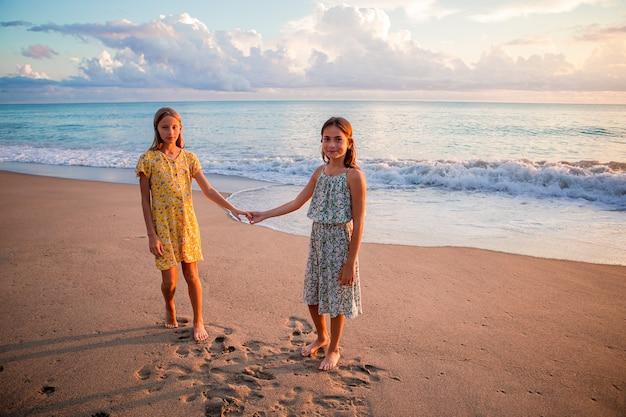 Garotinhas engraçadas e felizes se divertem muito na praia tropical brincando juntas