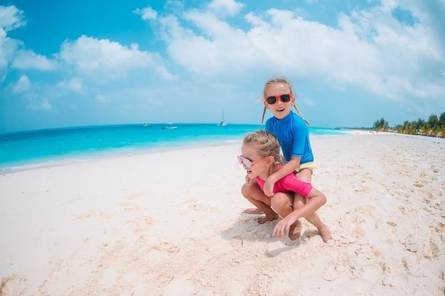 Garotinhas engraçadas felizes se divertem muito na praia tropical brincando juntas.