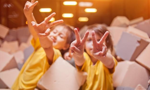 Garotinhas felizes brincam e se divertem em uma piscina seca com cubos paralon em um centro de entretenimento infantil e mostram os dedos, símbolo de paz e vitória