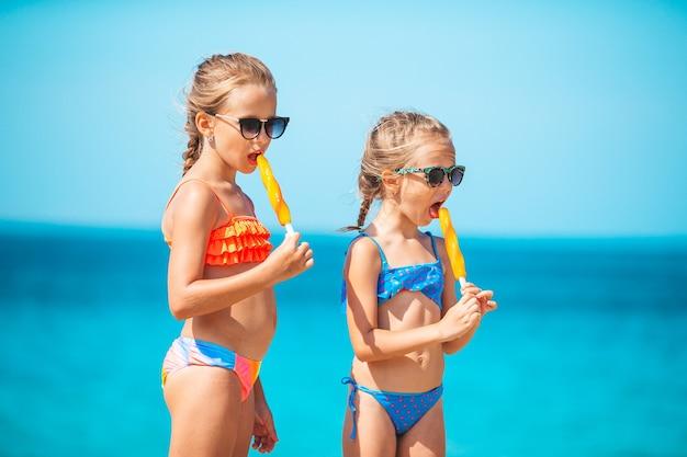 Garotinhas felizes comendo sorvete durante as férias na praia, pessoas, crianças, amigos e conceito de amizade