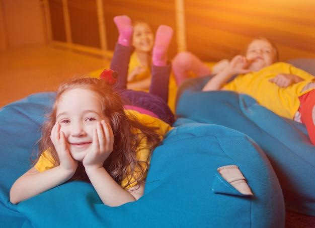 Garotinhas felizes deitadas na bolsa da cadeira no centro de entretenimento infantil