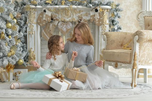 Garotinhas fofas com presentes perto da árvore de natal decorada