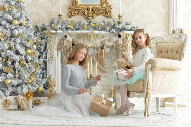 Garotinhas fofas com um presente posando em um quarto decorado para o feriado de natal