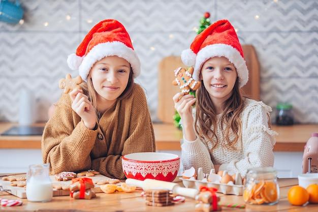 Garotinhas juntas cozinhando biscoitos de natal em casa na cozinha