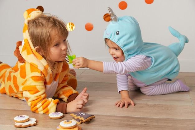 Garotinhas lindas com fantasia de girafa e narval brincam na festa de halloween em casa