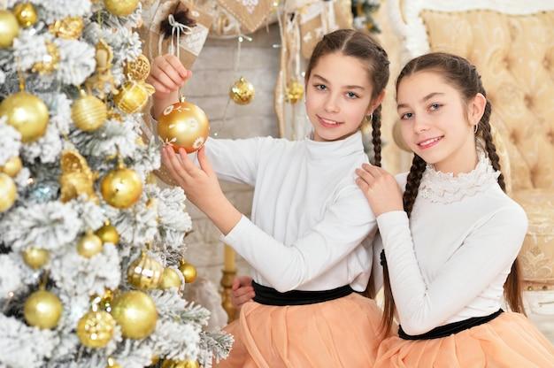 Garotinhas lindas decorando a árvore de natal e posando em casa