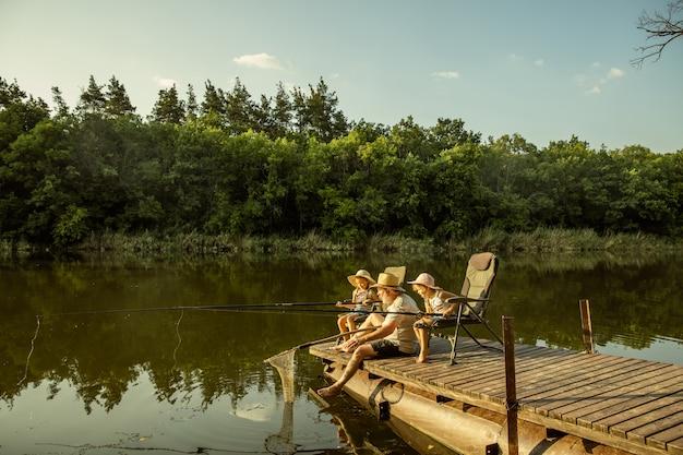 Garotinhas lindas e o avô estão pescando no lago ou rio