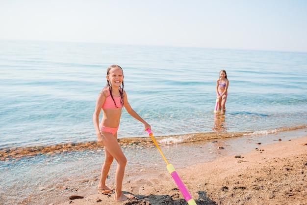 Garotinhas se divertindo em uma praia tropical durante as férias de verão brincando juntas