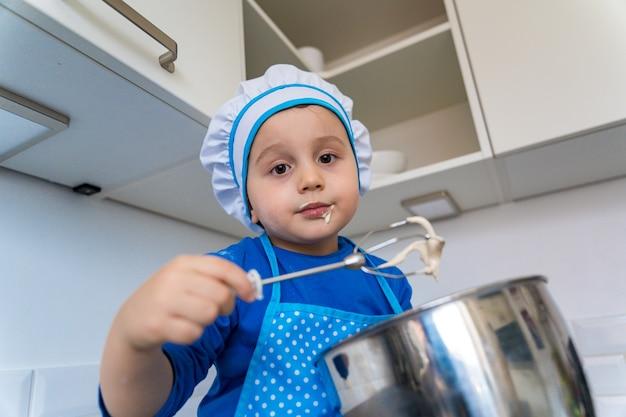 Garotinho adorável ajudando e fazendo torta de maçã na cozinha da casa
