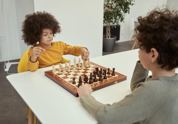 Garotinho adorável com cabelo afro se mexendo enquanto joga xadrez com o amigo sentado