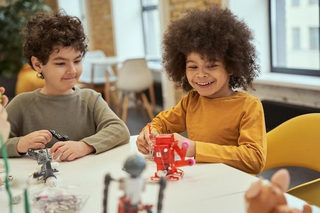 Garotinho adorável com cabelo afro sorrindo enquanto brinca com um brinquedo técnico e passa o tempo com