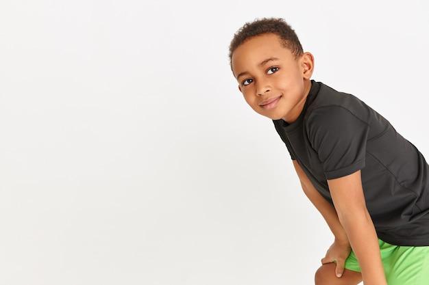 Garotinho adorável com camiseta preta e shorts verdes descansando durante o treino cardiovascular, mantendo as mãos acima dos joelhos