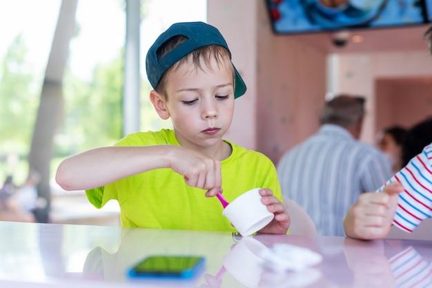 Garotinho adorável comendo sorvete de iogurte congelado em um café da cidade
