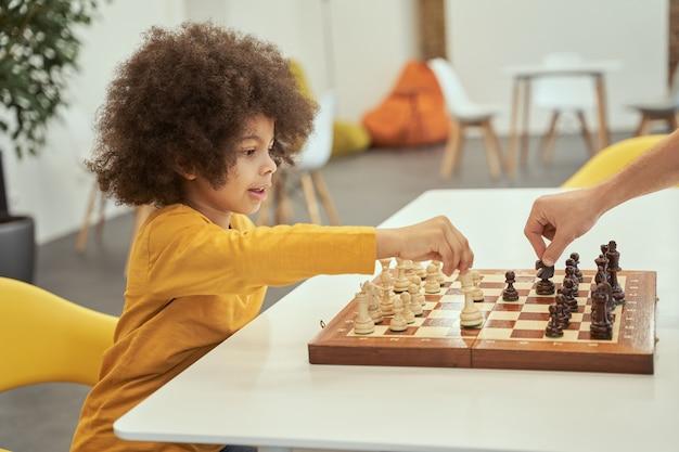 Garotinho adorável fazendo uma jogada jogando xadrez com um adulto sentado à mesa dentro de casa