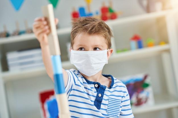 Garotinho adorável no jardim de infância com máscara devido à pandemia de coronavírus