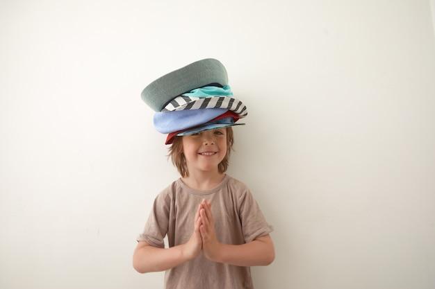Garotinho adorável usando chapéus diferentes na cabeça