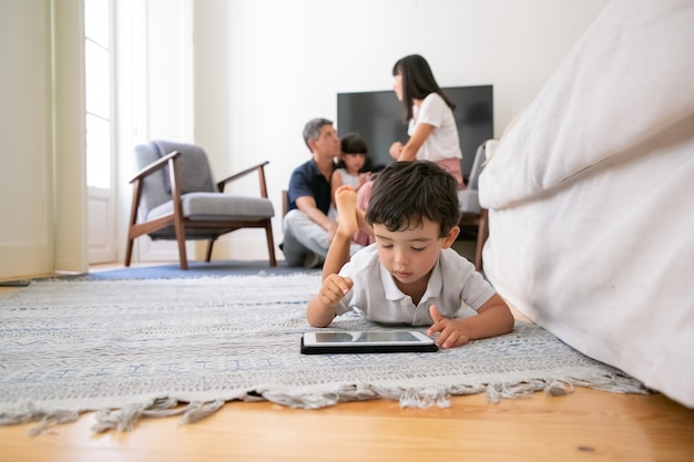 Garotinho adorável usando tablet, deitado no chão da sala de estar enquanto pais e irmã sentados juntos