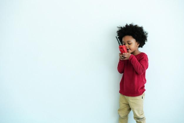 Garotinho afro-americano feliz em brincar de conversar com brinquedo walkie-talkie rádio