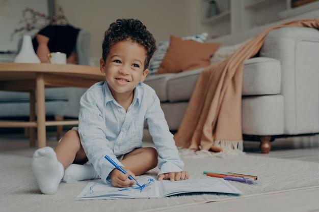 Garotinho afro sentado no chão e desenhando com canetas de feltro coloridas