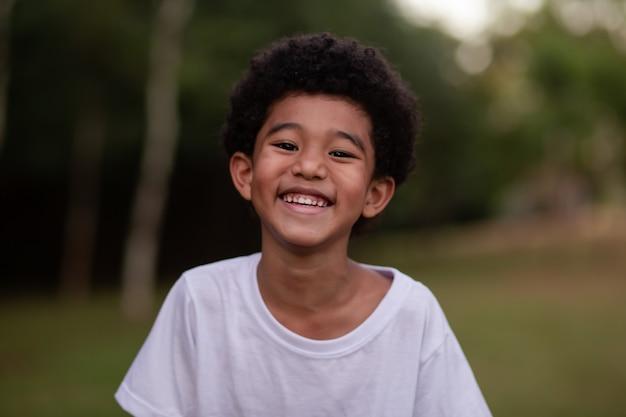Garotinho afro sorrindo para a câmera no parque