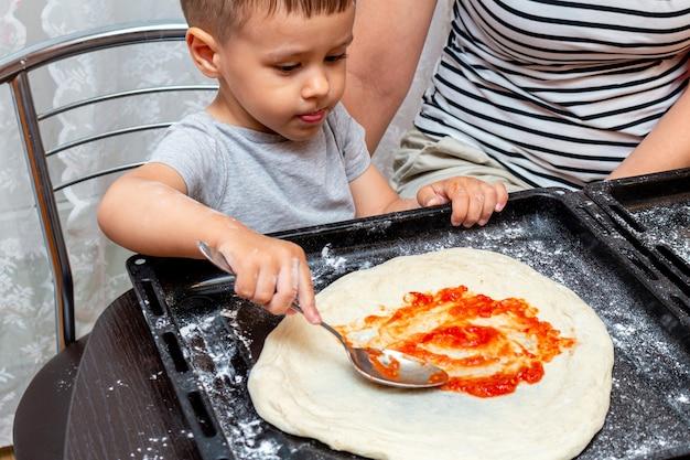 Garotinho, ajudando a mãe a fazer pizza em casa