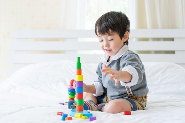 Garotinho alegre com brinquedo de madeira colorido