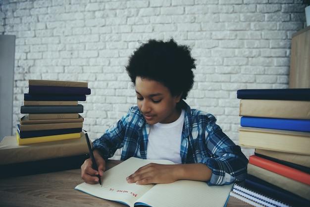 Garotinho americano africano faz lição de casa em casa