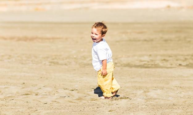 Garotinho andando em uma bela praia tropical