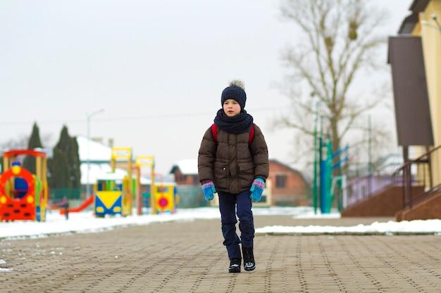 Garotinho andando no parque. criança saindo para uma caminhada depois da escola com uma mochila escolar no inverno. as crianças fazem atividades ao ar livre ao ar livre. conceito de modo de vida saudável.
